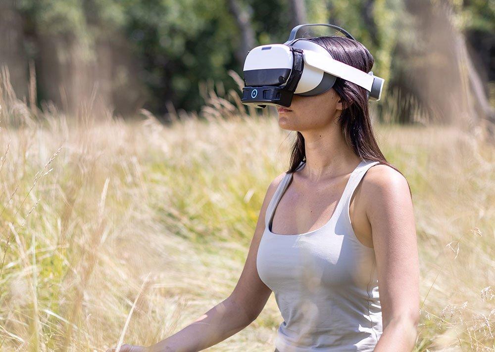 woman wearing virtual reality headset in a field